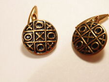 Gold colored cufflinks with antiqued face accenting a tic-tac-toe game