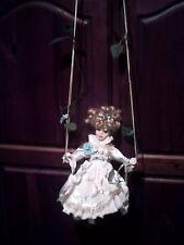 jolie poupée porcelaine sur balancoire -