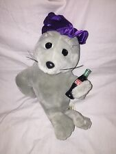 Coca Cola Advertising Seal - 1998 - Purple Cap Holding A Bottle Of Coca Cola