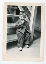 Adorable  little boy in over-sized clothing . vintage snapshot  photo