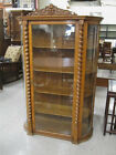 AN OAK AND CURVED GLASS CHINA CABINET, American, c Lot 213