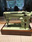 green vintage Singer sewing machine model 319W and accessories