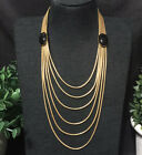 Gold tone layered multi strand snake chain necklace with 2 black glass cabochons