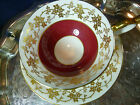 AYNSLEY  TEA CUP AND SAUCER  RED BAND FOLIAGE IN GOLD GILT STRIKING DUO  c1930