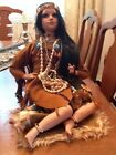 NATIVE AMERICAN PORCELAIN DOLL SITTING BROWN SUEDE DRESSHEADBAND JEWELRY ACCES
