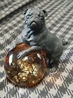 Vintage solid metal black pug dog statue with amber colored glass globe