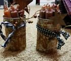 2 rusty primitive/country cans with 8 Grubby Candles in each rusty stars