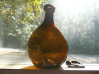 OPEN PONTIL FREE BLOWN AMBER CHESTNUT SADDLE TYPE FLASK WITH CRUDE GLOBBY LIP