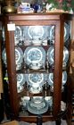 Vintage bow front mirrored china cabinet full of vintage Currier and Ives china